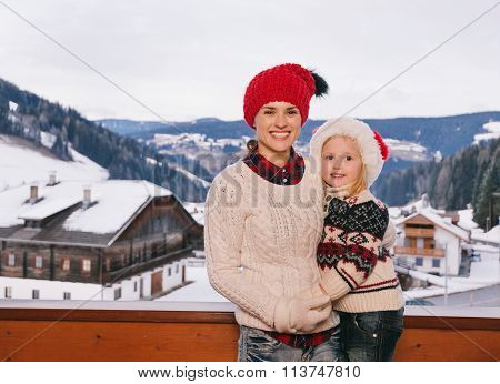 Mother And Child Standing On Balcony Overlooking Mountains
