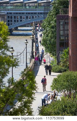 LONDON, UK - SEPTEMBER 10, 2015: Lots of people walking on southbank. City of London view from the r