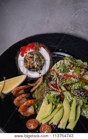 Salad of lettuce, avocado, sesame and shrimp
