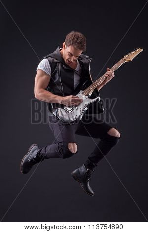 Attractive male guitarist with a cool musical instrument