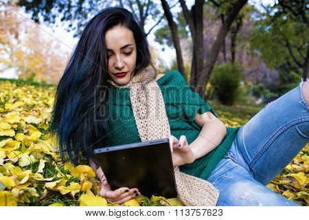 Beautiful Young Woman Whit Tablet In The Park