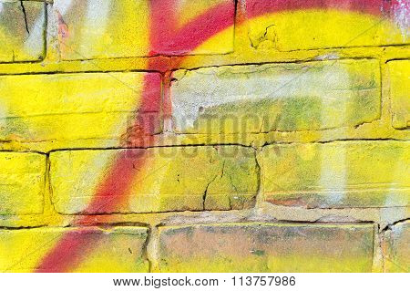 Detail of a red and yellow graffiti on a brick wall