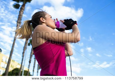 Young Blonde Sportswoman While Drinking Water After Running
