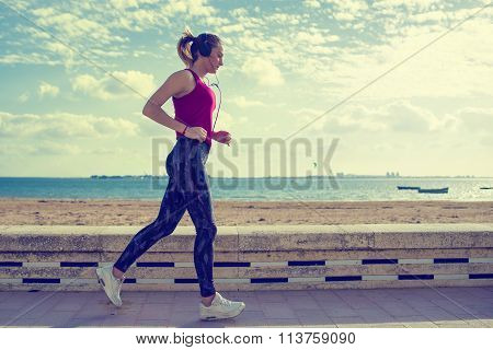 Young Blonde Sportswoman Running In The Beach