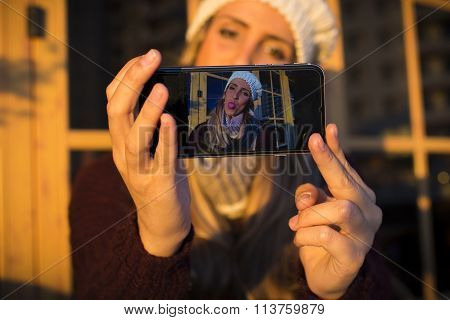 Young Woman Making Selfie On Her Phone And Showing Tongue