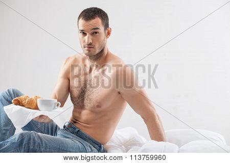 Attractive fit guy is serving food in bedroom
