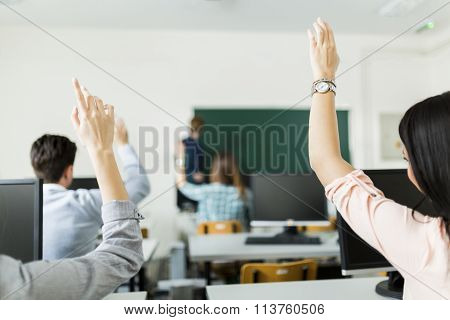 Young Students Raising Hands In A Classroom