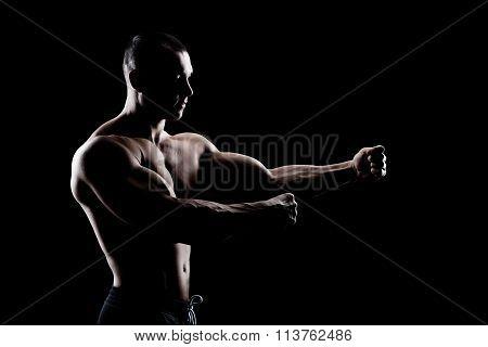 bodybuilder demonstrates biceps on a dark background