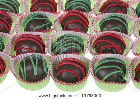 Cake balls with red and green candy stripping in green and red liners on white background
