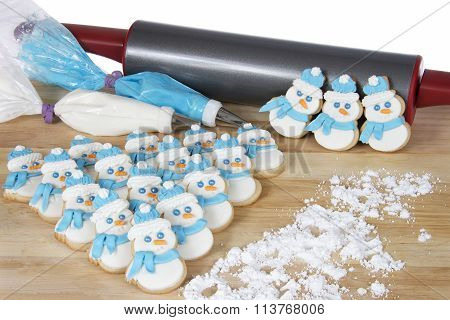Snowmen sugar cookies in triangle arrangement on wood table with rolling pin and frosting bags