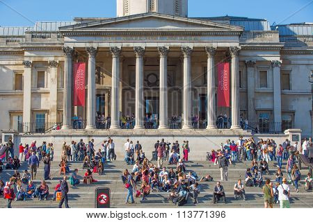 LONDON, UK - SEPTEMBER 10, 2015: Lots of people and tourists on the Trafalgar square in hot summer d