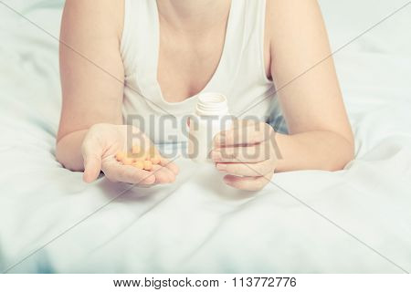 Woman In Her Pajamas In Bed Holding Yellow Pills