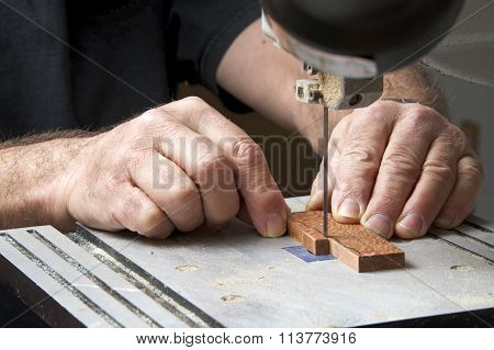Male hands holding a small piece of wood precision cutting on a table top jig saw