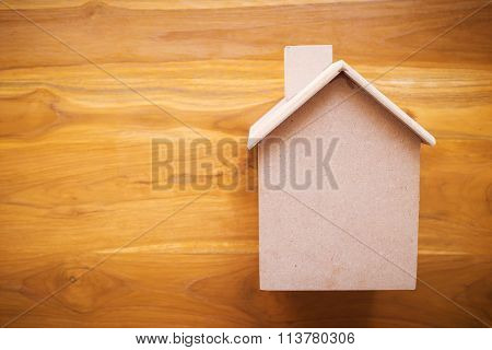 Small Wood House Model On Brown Wooden Background