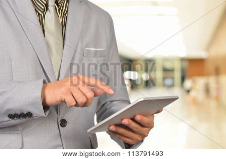 Young Business Man Browsing Web On Tablet At The Airport.