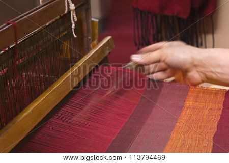 Weaver working on the old loom