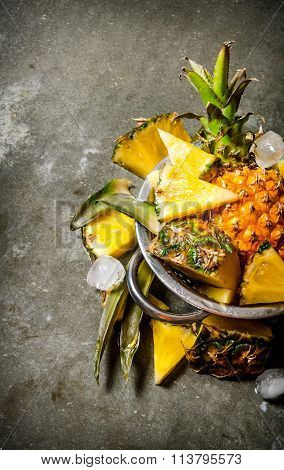 Slices Of Pineapple From A Whole Pineapple , Leaves And Ice In A Saucepan.