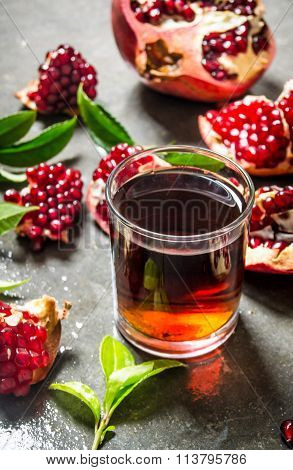 The Pomegranate Juice In A Glass With Pieces Of Pomegranate And Leaves.