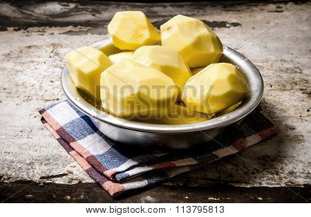 The Peeled Potatoes In A Metal Bowl On The Rustic Background .
