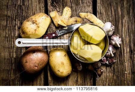 The Peeled Potatoes In A Saucepan With Garlic And Knife On Wooden Background .
