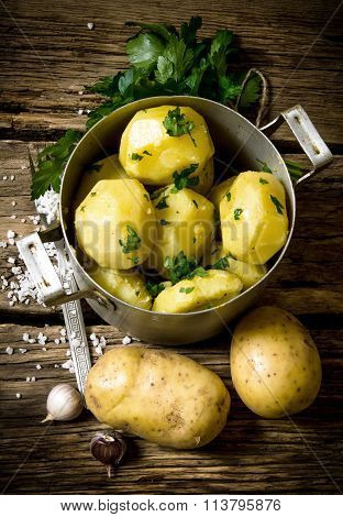 Boiled Potatoes With Herbs And Salt On A Wooden Table .