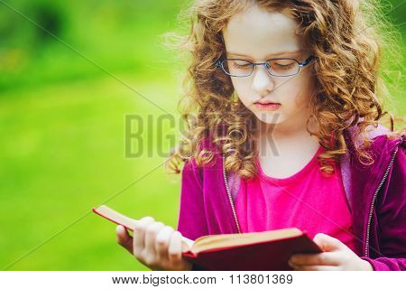 Little Girl In Eyeglasses Reading The Book In Autumn Park. Education Concept.
