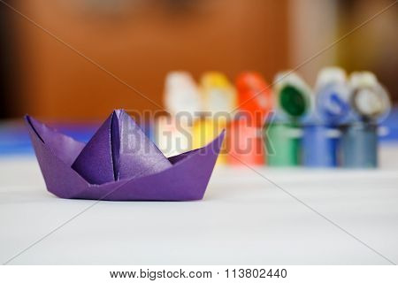 Origami paper boat violet color in front of jars with multi colored paints.
