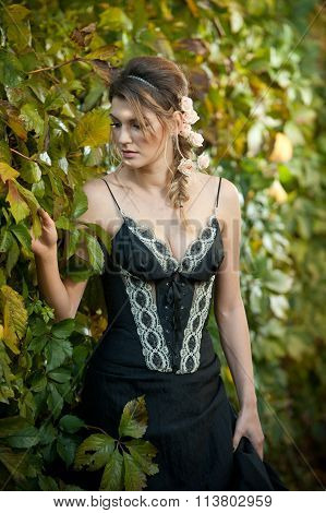Beautiful sensual woman with roses in hair posing near a wall of green leaves. Young female in black