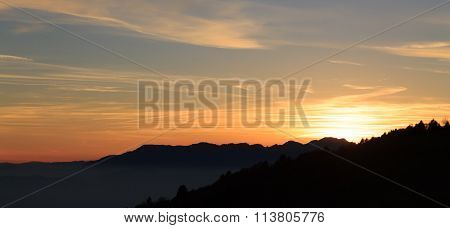 Mountain silhoutte over clouds . sky at twilight
