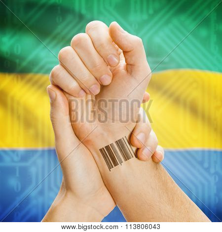 Barcode Id Number On Wrist And National Flag On Background - Gabon