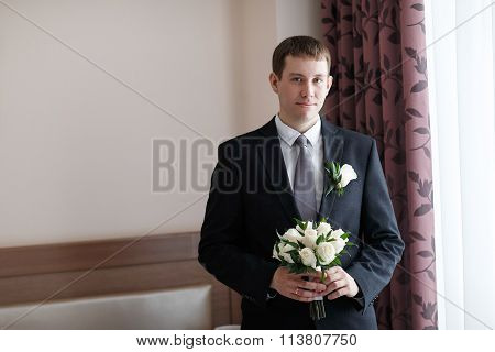 Man Holding A Bouquet Of The Bride At A Wedding