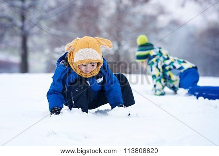 Two Boys, Brothers, Playing In The Snow With Snowballs