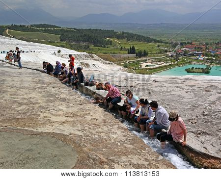 Pamukkale, Turkey - April 26, 2015: Tourists Feet Immersed In Water Flows Coming From The Travertine