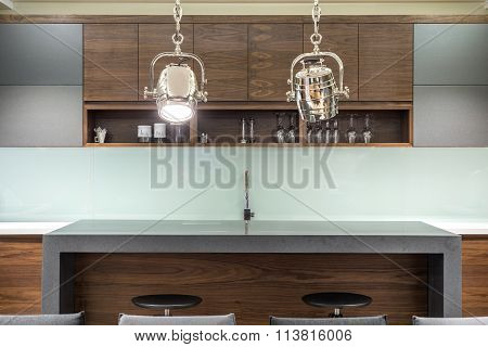 House Bar With Stools And Two Silver Reflector As Chandelier