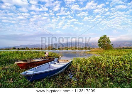 Two Fishing Boats By The Lakeside During Hot Sunny Day