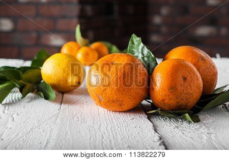 Tangerines And Lemons With Leaves On A Wooden Background