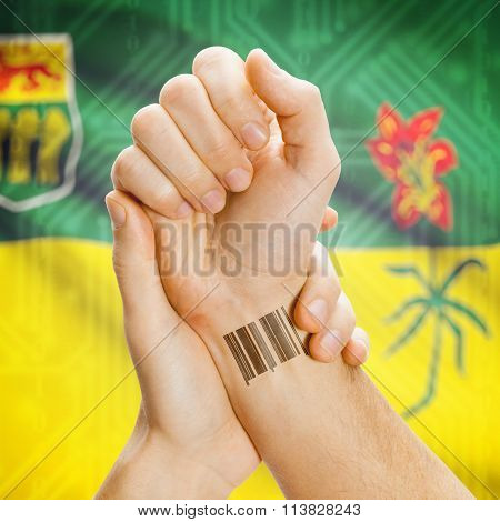 Barcode Id Number On Wrist With Canadian Province Flag On Background - Saskatchewan