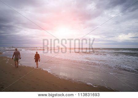 Two People Walking At Seashore