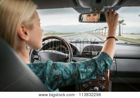Woman In Car Look In Rear View Mirror