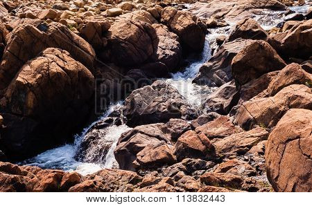 Stream Flowing And Splashing Among Bare Red Rocks