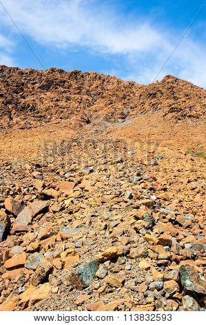 Dry Yellow Broken Rocks On Mountain Slope Against Sky