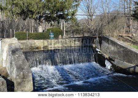 a concrete spillway with water falling