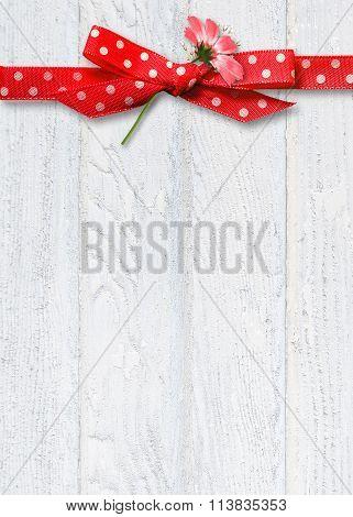 daisy in red polka dot ribbon on wood
