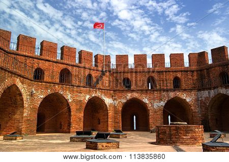 Red Tower Of Red Brick With A Turkish Flag And The Blue Sky.
