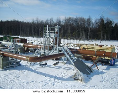 Platform of construction of pipelines. Booster pump station. Snow-covered area of the pipeline.
