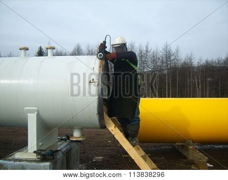 Russia, Sakhalin - November 15, 2014: Clarification from a rust of a place of future welding. Welding of the pipeline.