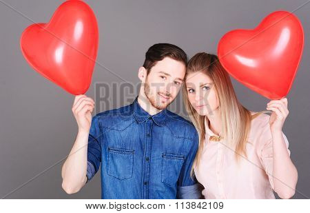 Love couple holding heart balloons