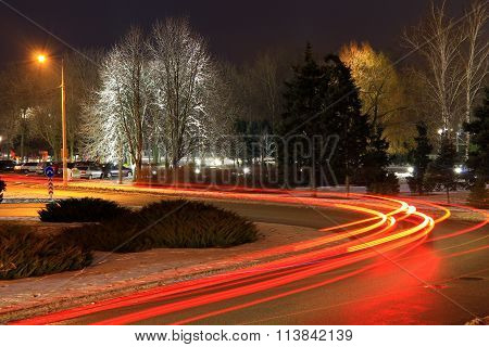 The lights of cars on the road in winter.