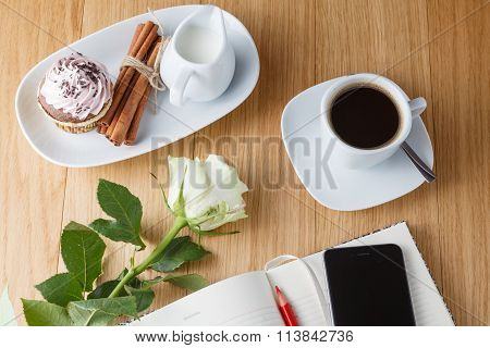 Close Up Of Cup Of Coffee And Notebook On A Wooden Table