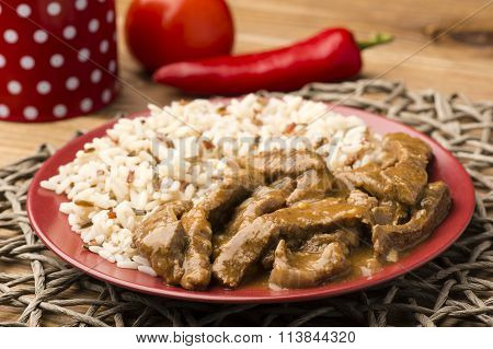 Stewed beef and rice on the red plate on brown wooden background.